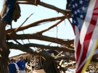 Two insurance adjusters survey a destroyed home in Moore, Oklahoma.