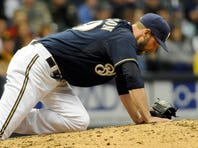 Brewers pitcher Jim Henderson reacts after hurting his leg in the ninth inning against the Pirates on Friday.