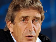 In this Feb. 18, 2013 file photo, Malaga's coach Manuel Pellegrini, from Chile, attends a news conference before a soccer training session at FC Porto's Dragao stadium in Porto, Portugal. Manchester City has hired Pellegrini as the club's new manager.