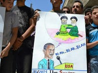 In this citizen journalism image, anti-Syrian regime protesters hold a placard with a caricature of President Obama, below the Hezbollah leader and Iran's supreme leader, on June 7 in northern Syria.
