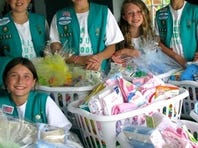 A local Girl Scout troop prepares baskets to be delivered to homeless babies for the Bless-A-Baby program of Bright Blessings.