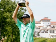 Bill Haas hoists the trophy after winning the AT,T National at Congressional Country Club.