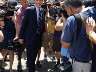 Former New York governor Eliot Spitzer is thronged by media as he collects signatures to get his name on the ballot for New York City comptroller.