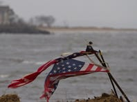 A tattered flag blows in the stiff breeze as it sits planted on an empty bay front lot in Union Beach, N.J., in February 2013.
