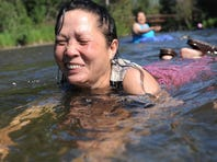 Kan Kil floats face-first in the cool waters of Campbell Creek while beating the heat on Tuesday in Anchorage. The city broke a record on Tuesday for hitting 70 degrees or more for the 14th straight day.