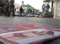 An couple on a Las Vegas Strip sidewalk push a toddler in a stroller past a discarded pamphlet advertising exotic dancers.