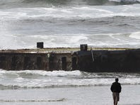 A man looks at the tsunami dock that washed ashore on Agate Beach in Newport, Ore.