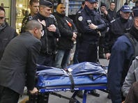 Kurds react as the bodies of three killed Kurdish women are removed from a Paris building Thursday.