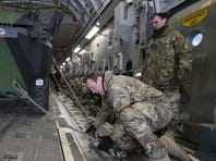 A British military personnel fixes a French army medical carrier inside a British C17 transport plane prior to takeoff at an army base north of Paris.
