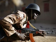 A Malian soldier takes cover behind a truck during exchanges of fire with jihadists in Gao, northern Mali, Sunday.