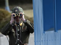 A North Korean soldier looks at the southern side through a pair of binoculars at the border village of the Panmunjom (DMZ) that has separated the two Koreas since the Korean War.