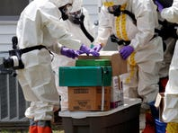 Federal agents wearing hazardous material suits and breathing apparatus inspect the home and possessions in the West Hills Subdivision house of Paul Kevin Curtis in Corinth, Miss., on Friday.