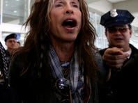 Steven Tyler of Aerosmith  is mobbed by reporters as he makes his way to his waiting van upon arrival from Melbourne Sunday.