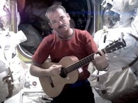 This image provided by NASA shows astronaut Chris Hadfield recording the first music video from space Sunday May 12, 2013. The song was his cover version of David Bowie's 'Space Oddity.'