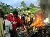 In this Feb. 6, 2013 file photo, hundreds of bystanders watch Helen Rumbali, a woman accused of witchcraft, being burned alive in the Western Highlands provincial capital of Mount Hagen in Papua New Guinea.