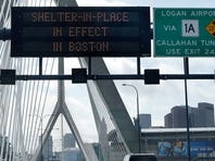 "A message calling for citizens of Boston to ""Shelter in Place"" flashes on a sign on I-93 near the Zakim Bridge in Boston on Friday."