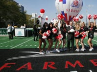 Paul Patsis, president of Market Management for Farmers Insurance, center, poses with Los Angeles Kings cheerleaders during a ceremony naming a new proposed NFL football stadium in Los Angeles.
