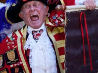 A Town Crier reads an announcement about the birth of a baby boy to Prince William and Catherine, Duchess of Cambridge, in London on Monday.
