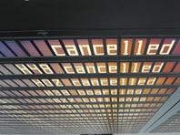 Sandy's having an impact on flights across the globe. Here, a flier a Germany's Munich Airport walks in front of a departure board highlighting cancelled flights to the U.S. on Oct. 29, 2012.