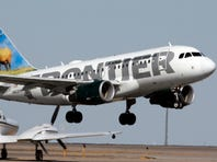 A small plane waits while a Frontier Airlines airplane lifts off from Denver International Airport on Sept. 27, 2007.