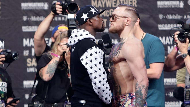 Floyd Mayweather Jr., left, and Conor McGregor, of Ireland, facing each other for photos during a news conference at Barclays Center in New York last month.
