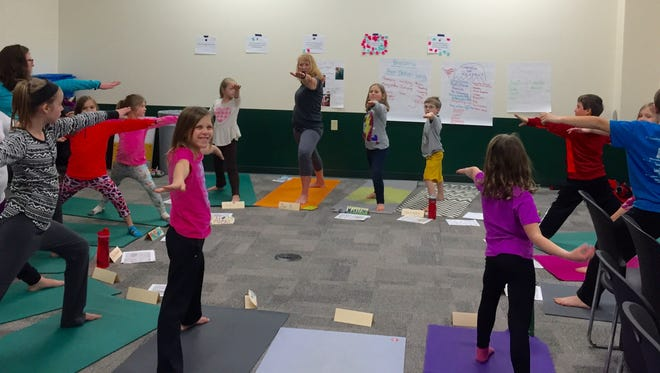 Children participate in a yoga class.