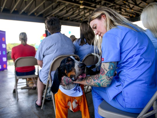 Starr Naylor sits with Hank, a blue tick hound up for
