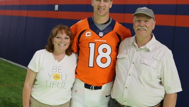 Peyton Manning and the Denver Broncos sent Kari Barnett Bollig the official photo she had taken with her football hero and her husband, Ed.
