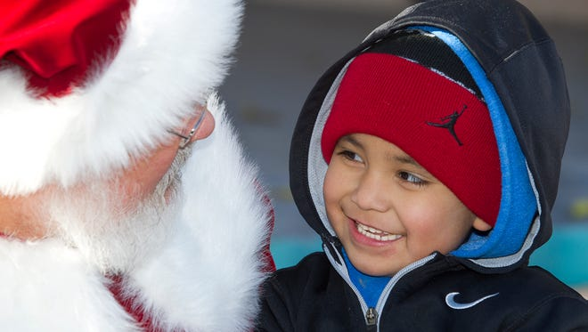 Tavian Lucero, 6, of Las Cruces is all smiles after asking Santa Claus for walkie talkies for Christmas at Winterfest Saturday afternoon at Klien Park.