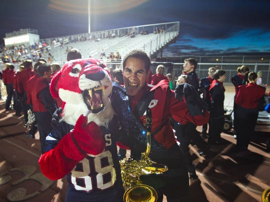 Gilbert Perry's mascot poses with a marching band member for a photo before the start of a high school football game.