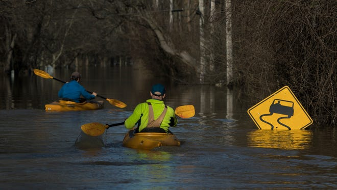 Kayakers make their way down River Road in Louisville, Kentucky after weekend flooding led to the highest point for the Ohio River's waters Monday. Feb. 26, 2018