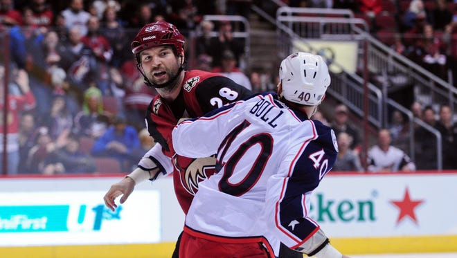 Arizona Coyotes left wing John Scott (28) and Columbus Blue Jackets right wing Jared Boll (40) fight during the second period at Gila River Arena.
