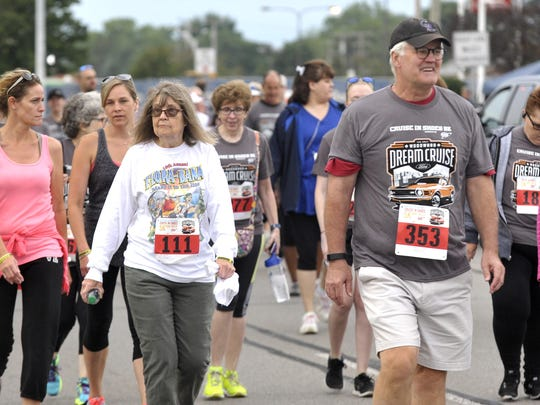 People participate in the Cruise in Shoes 5K run/walk as they head northbound in the southbound lanes of Woodward near 13 Mile on Saturday.