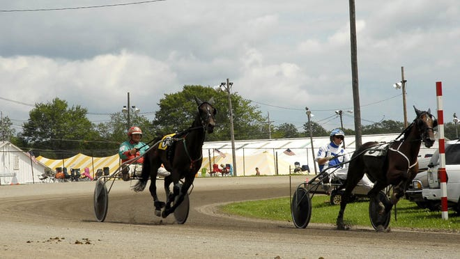 Horses race through the final turn during a harness-racing event at the Crawford County Fair in 2010. Harness races will be run at the Erie and Crawford county fairgrounds in August, though both fairs have been canceled because of the COVID-19 pandemic.