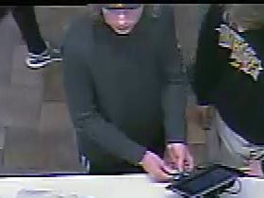 A man suspected of burglarizing a vehicle and using a stolen credit card is shown in an imagefrom a surveillance video.