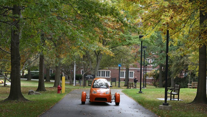 Elio Motors prototype three-wheeled car rolls onto campus at Nazareth College in Pittsford on Tuesday.  The appearance was part of an event announcing a partnership between Elio and Nazareth.  Nazareth students will take part in a contest to create the musical score that will accompany an Elio car commercial.