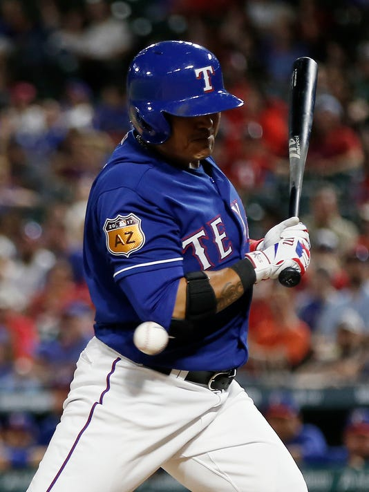 Texas Rangers Shin-Soo Choo is hit by a pitch from Kansas City Royals relief pitcher Matt Strahm during the sixth inning of an exhibition baseball game Friday, March 31, 2017, in Arlington, Texas. Texas won 3-0. (AP Photo/Brandon Wade)