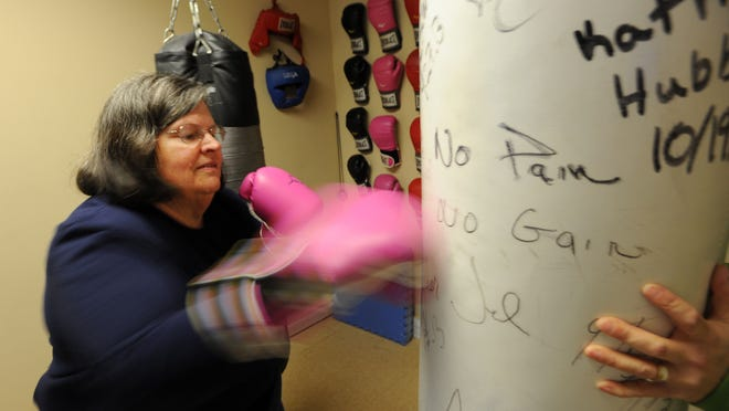Peggy Fellows, 64, punches a heavy bag at HubbMuscle. She currently holds the top spot in a contest among clients determining who lost the most inches in the past three months, having lost 22 3/4 inches.