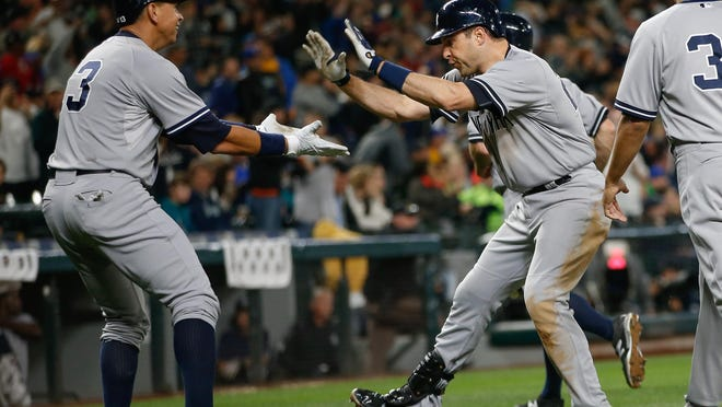 Mark Teixeira is congratulated by Alex Rodriguez after hitting a grand slam against the Seattle Mariners in the fifth inning on Monday. Teixeira's return to form has helped drive the Yankees' offense.