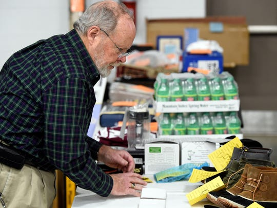 MIKE LAWRENCE / THE GLEANER  Lions Club member Mike Olsen organizes sale items for Monday's Lions Club Auction being produced at the HCC Sullivan Technical Center, February 8, 2016.
