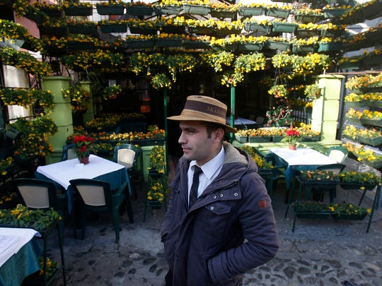 In this photo taken Tuesday, Dec. 13, 2016, a waiter waits for guests in front of a restaurant in the Skadarlija bohemian quarter, in Belgrade, Serbia. Belgrade has emerged as one of Europe's prime party destinations.