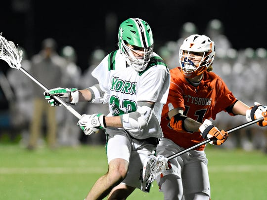 York College's Matt Whitcher, left, controls the ball while Gettysburg's Eric Carr defends during men's lacrosse action at York College of Pennsylvania in Spring Garden Township, Wednesday, March 7, 2018. Gettysburg would win the game 8-6. Dawn J. Sagert photo