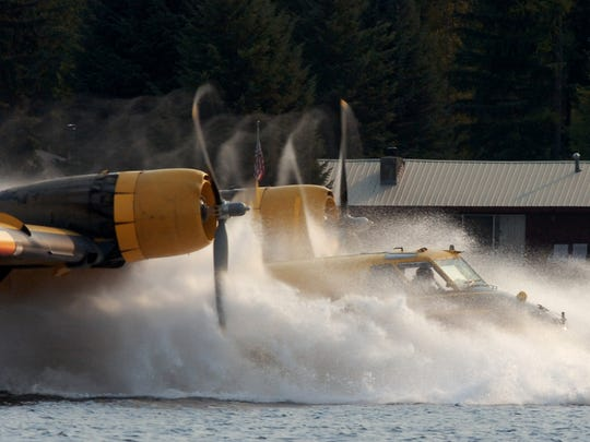"""A """"super-scooper"""" firefighting airplane kicks up a"""