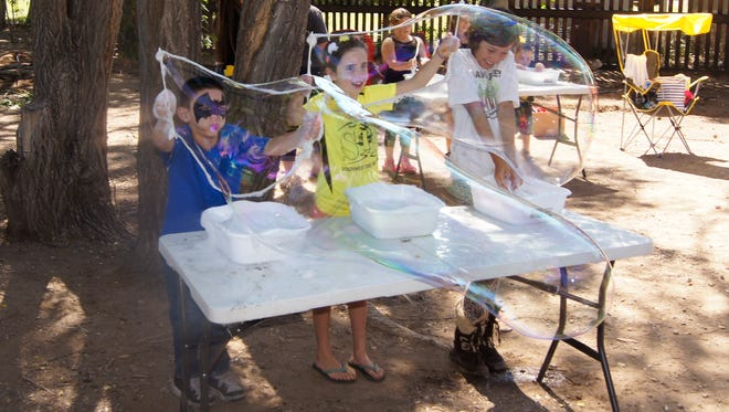 Youngsters try their hands at making bubbles at the Red Hot Children's Fiesta on Saturday in Penny Park.