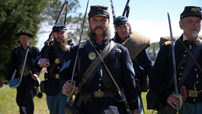 Christopher Lydick, center, leads a group of Civil War re-enactors as they march along a 10-mile route Friday from the St. Marks Lighthouse to Newport to camp for the night. The troops will then continue on the trail to Natural Bridge Battlefield Historic State Park, where they will stage the 152nd anniversary of the civil war battle that took place there.