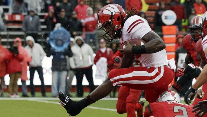 Wisconsin running back Melvin Gordon (25) leaps for a touchdown over Rutgers defensive back Gareef Glashen (2) during the first half of an NCAA college football game against Rutgers, Saturday, Nov. 1, 2014, in Piscataway, N.J.