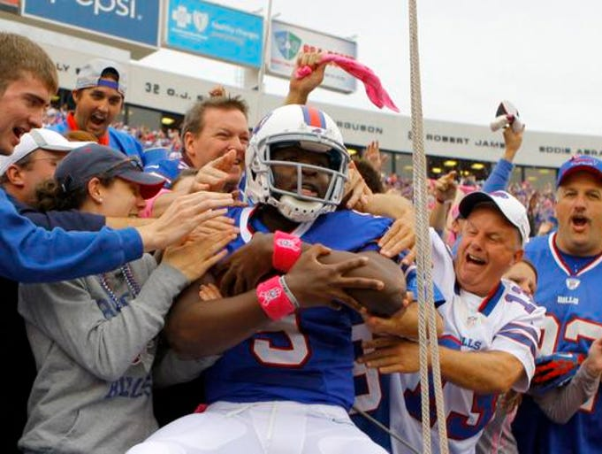 Buffalo Bills quarterback Thad Lewis (9) jumps in the crowd to celebrate his touchdown during the first quarter against the Cincinnati Bengals at Ralph Wilson Stadium.