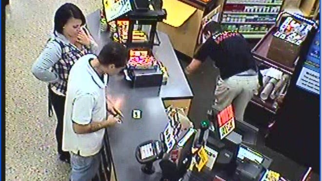 Surveillance photo of suspects using a debit card at Wawa in Brick.