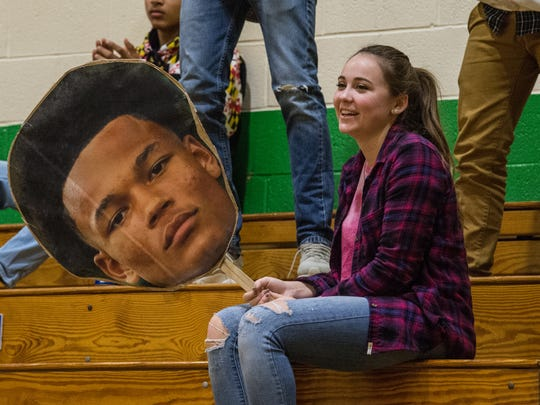 A fan holds a a sign of Josh Sproules' face during a game against Mardela on Thursday, Jan. 18, 2018.