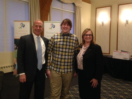 Adrian College President Jeffrey Docking, Adrian wrestler Clarence Kennedy and Adrian vice president Agnes Caldwell at a recent awards banquet. Adrian's heart screening may have saved Kennedy's life.